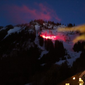 The skiers in Thollon come down the mountain with red flames, to welcome in the new year.